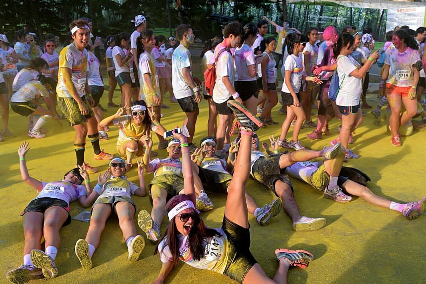 Participants of The Color Run rolling on the ground to get more coloured powder on themselves at Sentosa yesterday. At $50, the untimed 5km run's registration fee is nearly as high as that for much longer races such as the upcoming $58 Army Half Ma