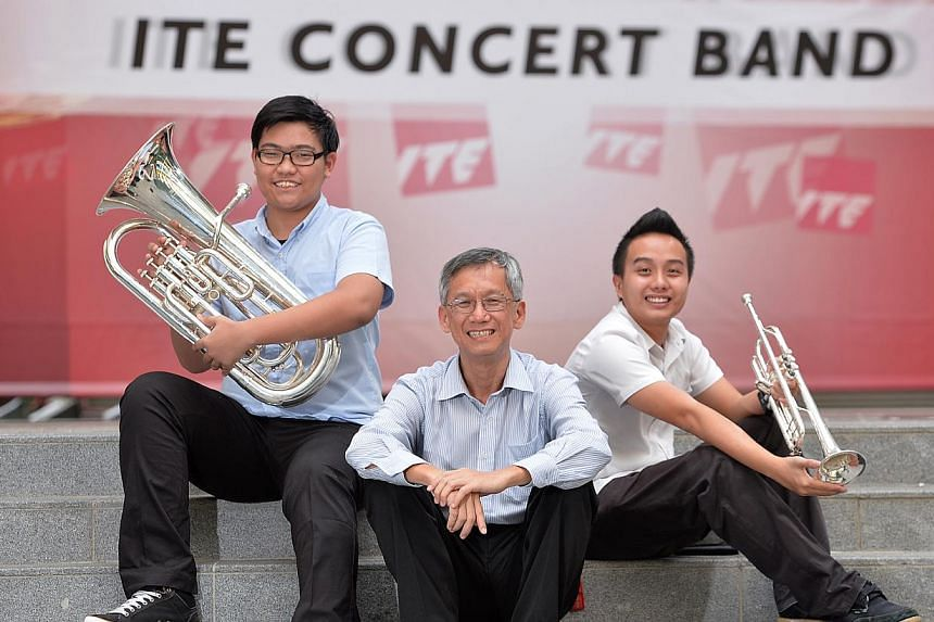 ITE College Central band members Muhammad Anwar Muhamat Ali (left) 18, who plays the euphonium, and trumpet player Adrian Tan (right) 19, with deputy principal Chong Leong Fatt. The two students will be part of the concert band performing tonight. --