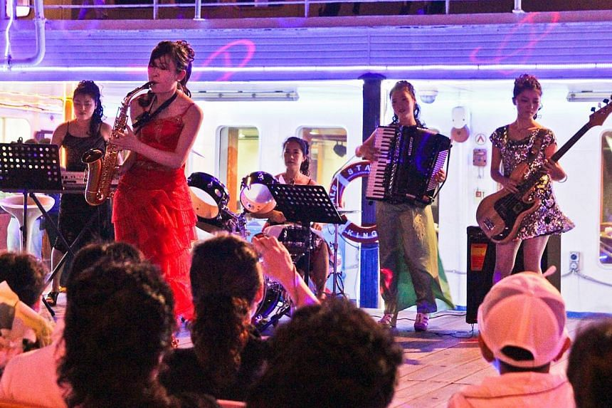 At night, some of the Royale Star's female crew members double as musicians (above) to entertain passengers, performing what they say are popular North Korean songs with Pyongyang-style dances. The ship travels from north-eastern Rajin port to the sc