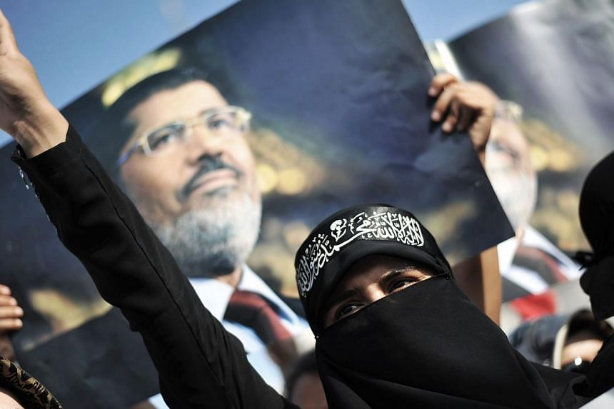 A woman protestor chants slogans in front of a poster of Egypt's ousted president Mohamed Mursi during a demonstration condemning the recent deadly military crackdown on pro-Morsi protesters in Cairo on Saturday, Aug 17, 2013, at New Mosque in Istanb