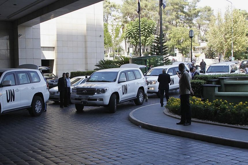 UN vehicles transporting a team of United Nations chemical weapons experts arrive in Damascus on Sunday, Aug 18, 2013. UN inspectors tasked with investigating whether chemical weapons have been used in the Syrian conflict arrived in Damascus on Sunda