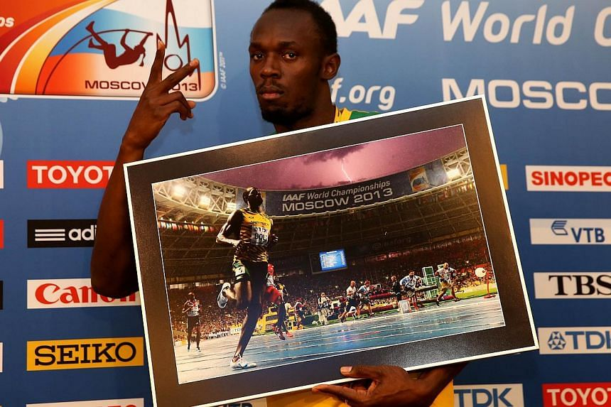 Jamaica's Usain Bolt poses with a print of a picture taken by AFP photographer Oliver Morin during the 100m final of Bolt prior to a press conference at the Luzhniki stadium in Moscow during the World Athletics Championships on August 17, 2013. Jamai