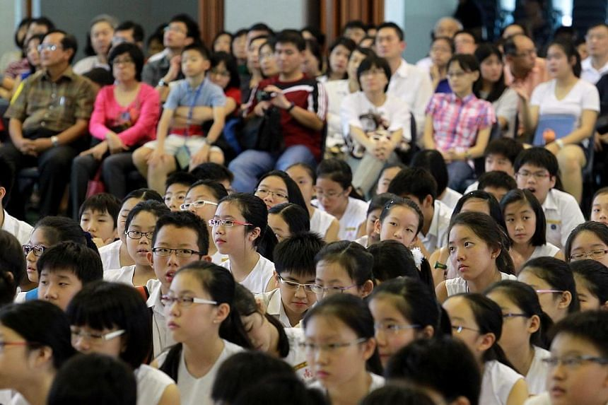 Pupils and parents awaiting the PSLE 2012 results at Nanyang Primary School. The PSLE T-score, long a source of stress for students and parents, will eventually be removed and replaced with bands similar to those used for O' and A' levels, said Prime