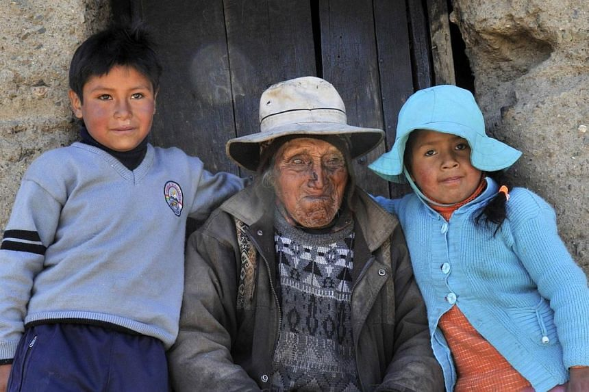 Bolivian Carmelo Flores Laura (centre) is accompanied by great-granchildren Edgar (left) and Gloria, outside his house in the community of Frasquia, 4,050m above sea level, on the foothills of the Illampu snowcapped mountain in the Bolivian Andes, so