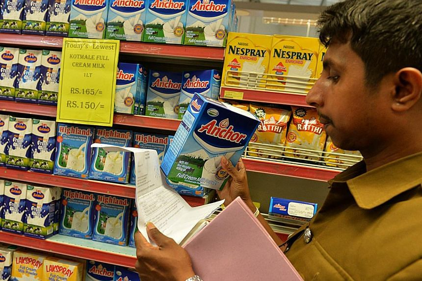 A Sri Lankan health inspector checks the batch code of a milk powder package in the capital Colombo on August 15, 2013.New Zealand's Fonterra, the world's top dairy exporter, said on Monday an injunction banning the sale of its products in Sri