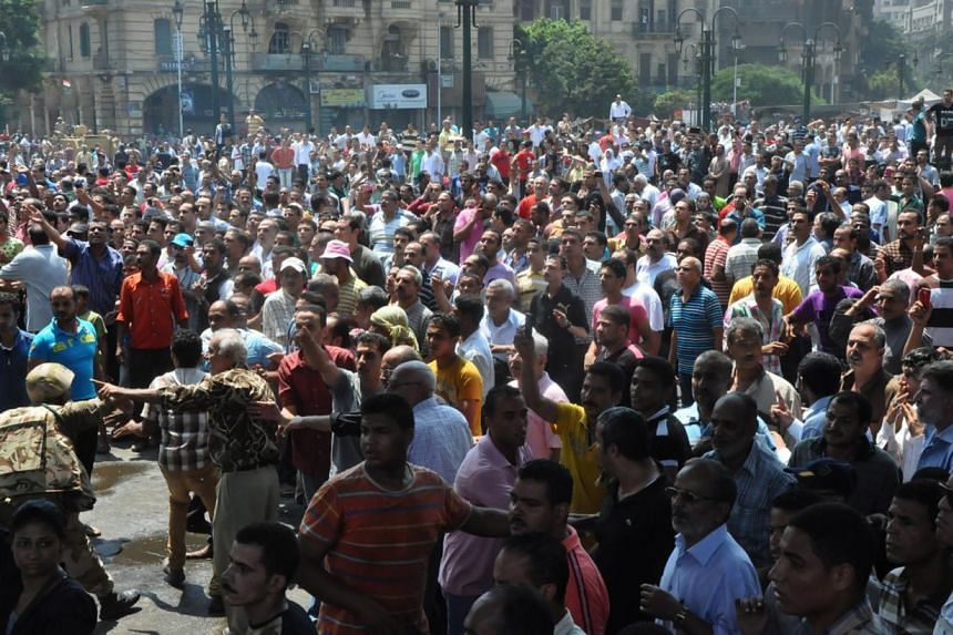 A member of Egyptian security forces, at left among others not seen, tries to keep angry crowds away from the al-Fatah mosque, where supporters of the Muslim Brotherhood barricade themselves, in Ramses Square, downtown Cairo, Egypt, Saturday, Aug. 17
