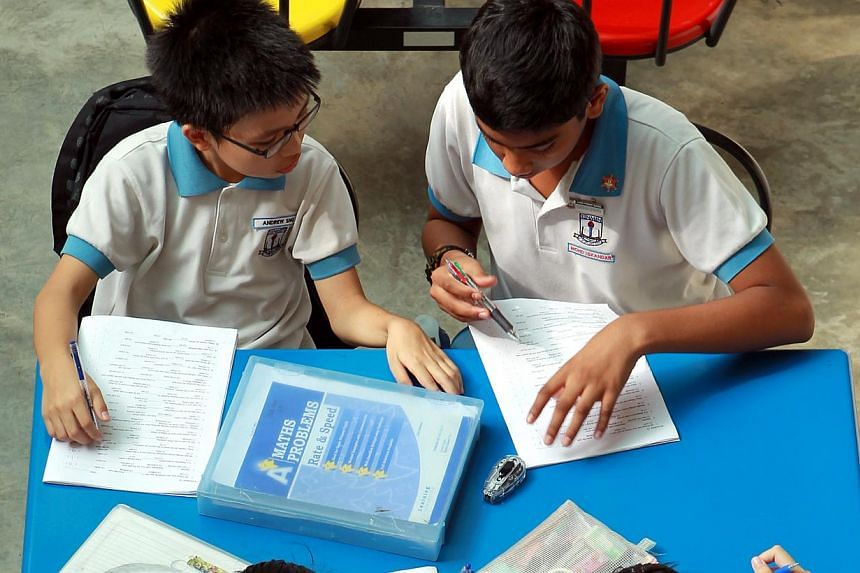 Xinmin Primary School students doing homework in the school compound. Edusave contributions will be extended to all children who are Singapore citizens aged seven to 16, the Ministry of Education announced on Monday. -- FILE PHOTO: SEAH KWANG PENG&nb