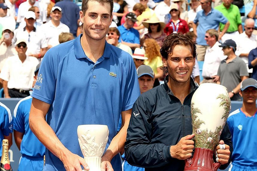 John Isner and Rafael Nadal of Spain pose for photographers at the trophy ceremony after the final of the Western & Southern Open on August 18, 2013 at Lindner Family Tennis Center in Cincinnati, Ohio. Rafael Nadal won the Cincinnati Masters for