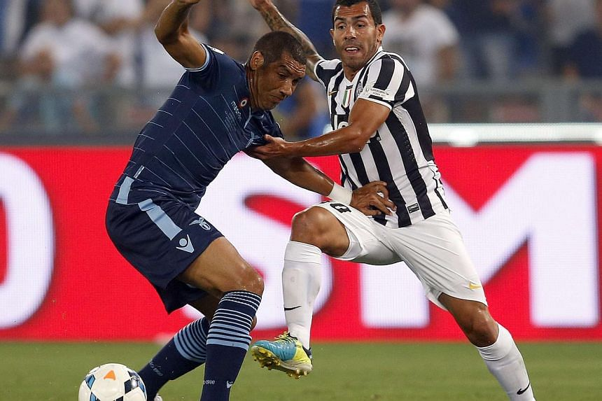 Juventus' Carlos Tevez (right) challenges Andre Dias of Lazio during their Italian Super Cup match at the Olympic stadium in Rome Aug 18, 2013. Carlos Tevez marked his Juventus debut with a goal as the Serie A champions thrashed Lazio 4-0 in the Ital