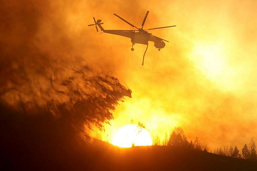 A helicopter makes a drop while battling the Beaver Creek Fire on Saturday, Aug 17, 2013 north of Hailey, Idaho. Firefighters mounted on Sunday an all-out ground and air attack on an Idaho wildfire that has forced the evacuation of some 2,250 homes a