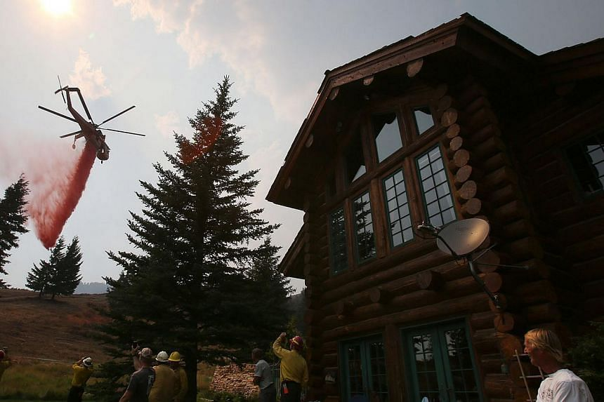 A helicopter makes a drop on a dozer line around a home to protect it from the Beaver Creek Fire on Sunday, Aug 18, 2013 in outside of Ketchum, Idaho. Firefighters mounted on Sunday an all-out ground and air attack on an Idaho wildfire that has force