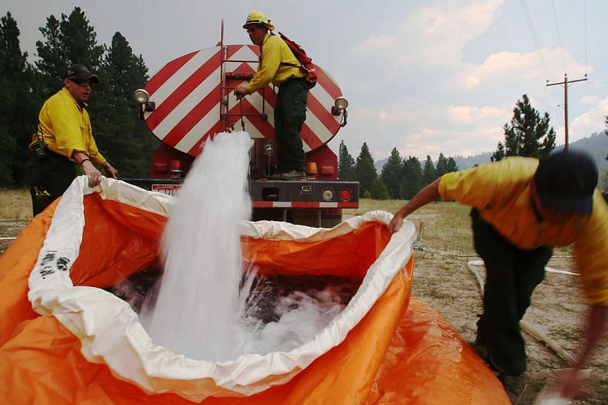 Members of the Mountain Home Fire Department fill a water reservoir called a pumpkin, with 1,800 gallons of water on Monday, Aug 12, 2013, as they prepare to defend homes from the more than 80,000-acre Elk Complex Fire burning near Pine, Idaho. Firef