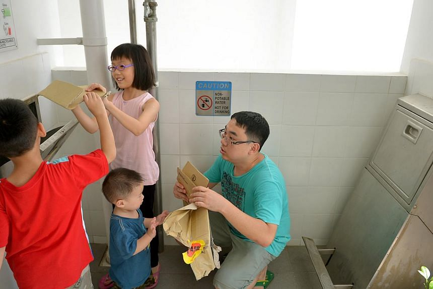 Mr Jeremy Tan with his children Clement, seven, Kacey, nine, and Kevin, two, at the recycling chute outside their flat in Punggol. Mr Tan says they can recycle up to several times a day as it is convenient to do so. -- ST PHOTO: KUA CHEE SIONG