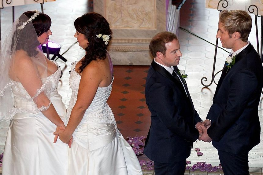 Richard Rawstorn (second right) with Richard Andrew (right) from Christchurch and Jess Ives (second left) and Rachel Briscoe (left) from the Bay of Islands celebrate during the first same sex marriage at the Rotorua Museum in Rotorua on Aug 19, 2013.