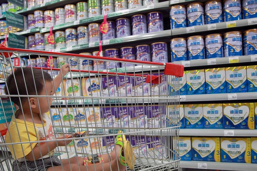 A baby sits in a shopping cart in a supermarket in Haikou, south China's Hainan province on Aug 7, 2013. More New Zealand milk products sold to China have been banned after elevated levels of nitrates were found, raising further concerns over quality