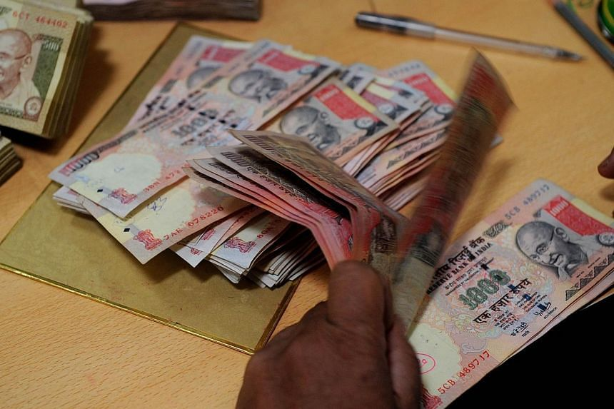 An employee counts Indian rupee notes at a bank in Mumbai on May 16, 2012. India's rupee hit a new low and shares slipped another 1.3 per cent on Monday on growing fears about the country's slowing economy and the government's ability to stem a deepe
