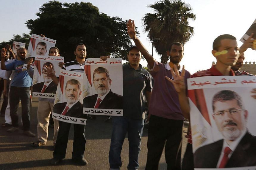 Supporters of deposed Egyptian President Mohamed Mursi hold up posters of him during a protest along Zahara street in Cairo on Aug 18, 2013.Egyptian authorities escalated their crackdown on deposed President Mohamed Mursi's Muslim Brother
