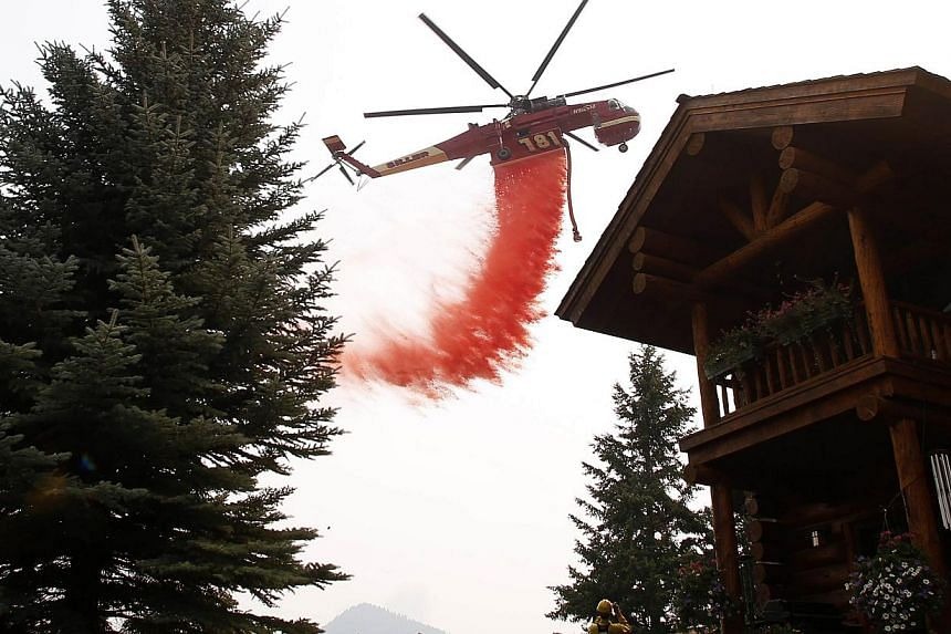 A helicopter tanker drops fire retardant near a home at the Beaver Creek wildfire outside Ketchum, Idaho, on Aug 18, 2013. Some 1,200 firefighters were on Monday battling a giant blaze threatening a ski resort in the US state of Idaho favoured by Hol