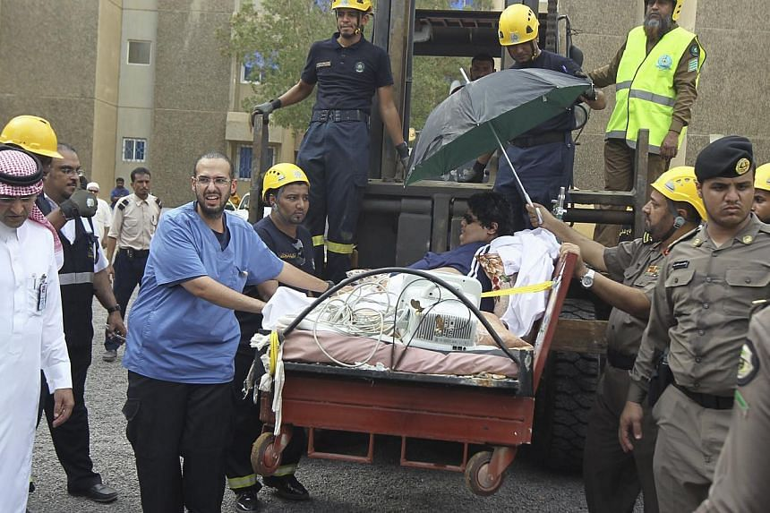 Saudi Civil Defence members use a forklift to move Khaled Mohsen Shaeri, 20, from his house in the Saudi city of Jizan, and airlifting him to the capital Riyadh for medical treatment, on Aug 19, 2013. -- PHOTO: REUTERS