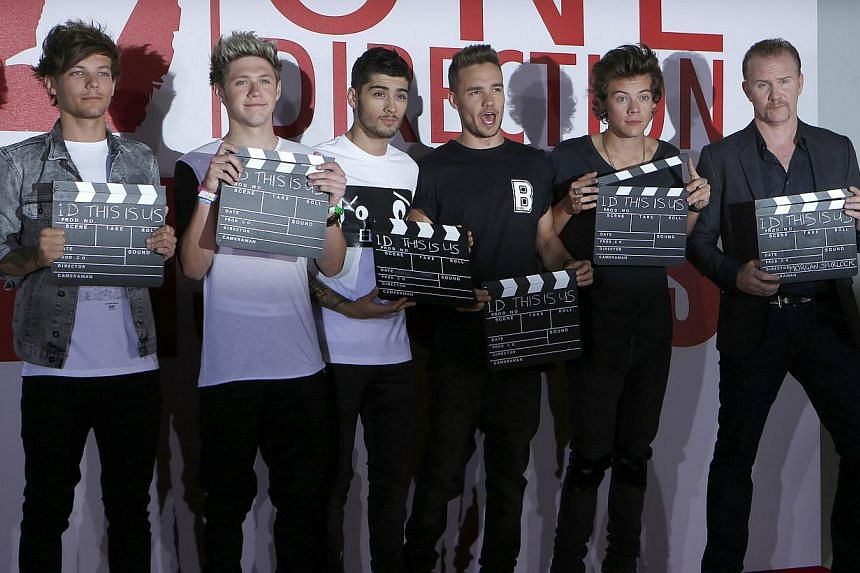 Members of the music group One Direction, Louis Tomlinson, Niall Horan, Zayne Malik, Liam Payne, Harry Styles, and Director Morgan Spurlock, pose for photographers during a photocall for their film 'ne Direction; This Is Us in London on Aug 19, 2013.