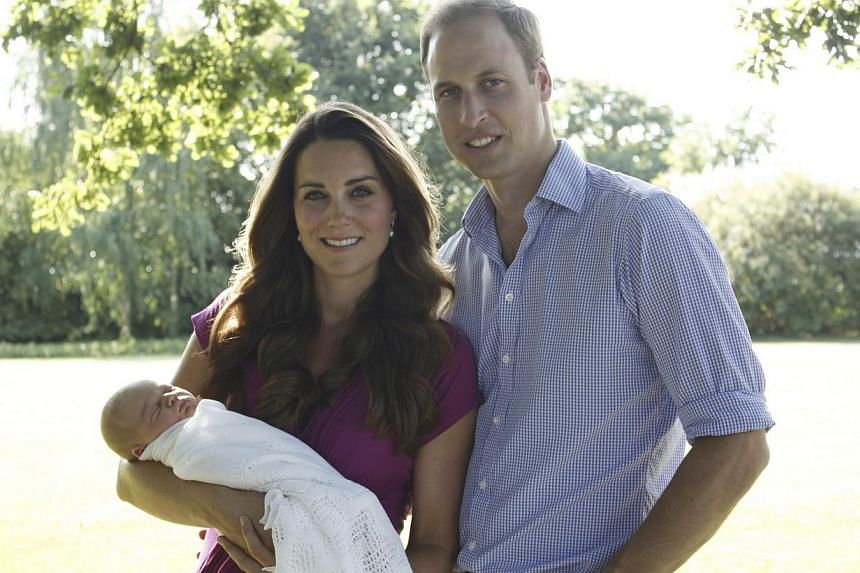 Britain's Prince William and his wife Catherine, Duchess of Cambridge, pose in the garden of the Middleton family home in Bucklebury, southern England, with their son Prince George, in this undated photograph released in London on Aug 19, 2013. -- PH
