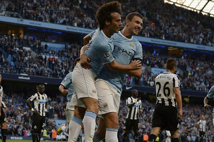 Manchester City's David Silva (left) celebrates scoring, with Edin Dzeko, against Newcastle United during their English Premier League soccer match at the Etihad Stadium in Manchester, northern England, on Aug 19, 2013.Manchester City started t