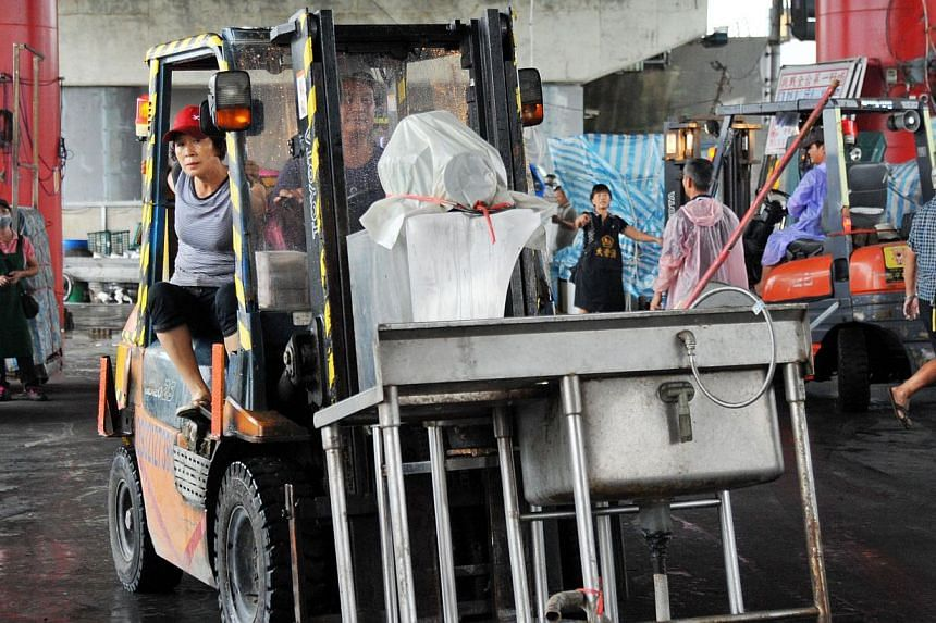 Residents move their food stands in preparation for Tropical Storm Trami in Taipei on Tuesday, Aug 20, 2013. Residents of some low-lying areas in the capital piled up sandbags. -- PHOTO: AFP