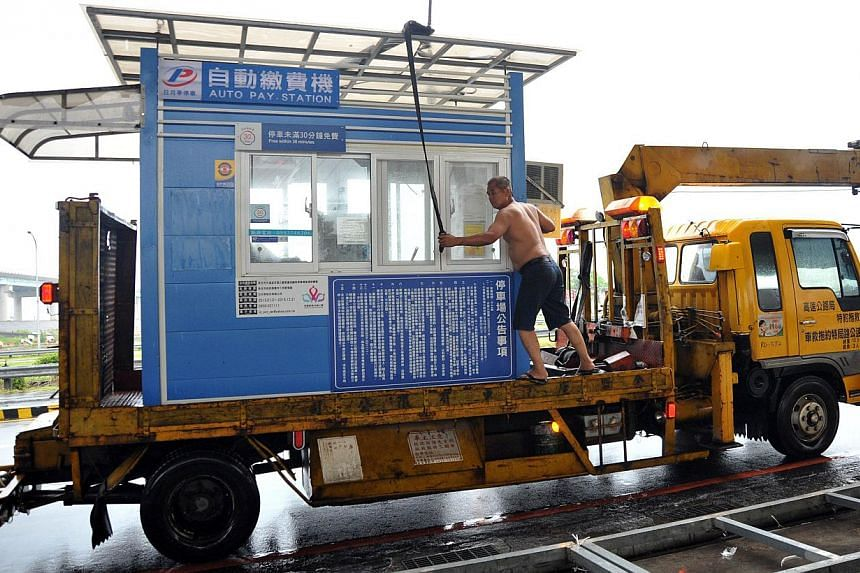 Taipei City Government engineering staff move an auto-pay station booth in preparation for Tropical Storm Trami in Taipei on Tuesday, Aug 20, 2013. Just last month, Typhoon Soulik battered Taiwan with torrential rain and powerful winds, leaving two p