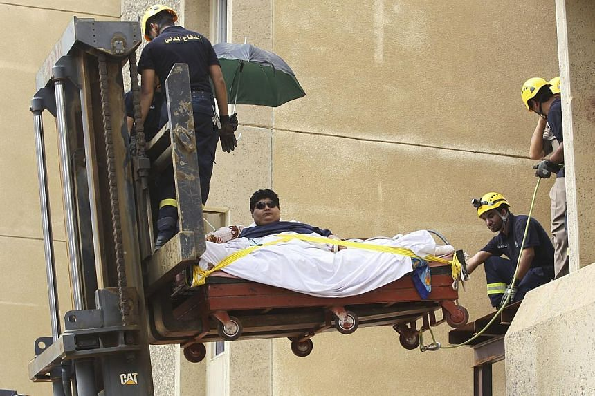 Saudi Civil Defence members use a forklift to move Khaled Mohsen Shairi, 20, from his house in the Saudi city of Jizan, and to be airlifted to the capital Riyadh for medical treatment, on Aug 19, 2013.-- PHOTO: REUTERS