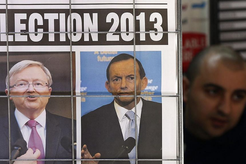 A man walks behind advertisement of a newspaper with pictures of Australian Prime Minister Kevin Rudd (left) and Opposition Leader Tony Abbott in central Sydney in this Aug 5, 2013 file photo. Media baron Rupert Murdoch threw his support firmly behin