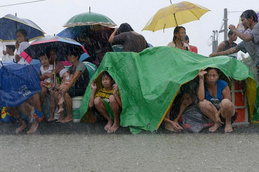 Residents take shelter from the rain after floodwaters inundated their homes in the farming town of Novaleta, some 26 kilometres outside Manila on Aug 19, 2013. Torrential rain paralysed large parts of the Philippine capital on August 19 as neck-deep