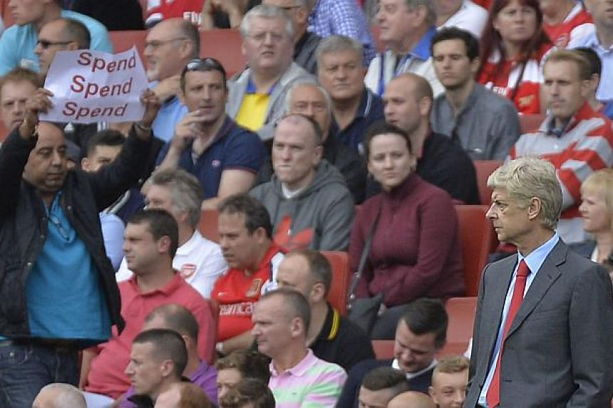 A fan holds a protest banner (left) as Arsenal's manager Arsene Wenger watches during their English Premier League soccer match against Aston Villa at Emirates Stadium in London on Aug 17, 2013. Wenger defended his transfer policy, reminding disgrunt