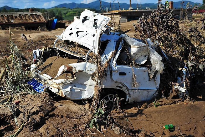 This picture taken on Aug 19, 2013, shows a damaged car after floods hit the Qingyuan Manchu autonomous county of Fushun, in north-east China's Liaoning province. Heavy rains killed 21 more people as flooding spread to north-west China, state media s