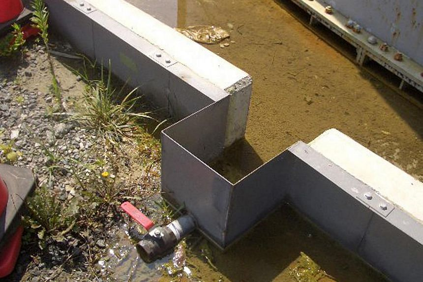 This hand out picture taken by Tokyo Electric Power Co (Tepco) on Aug 19, 2013, shows contaminated water which leaked from a water tank at Tepco's Fukushima Dai-ichi nuclear power plant at Okuma town in Fukushima prefecture. Japan will raise the seve