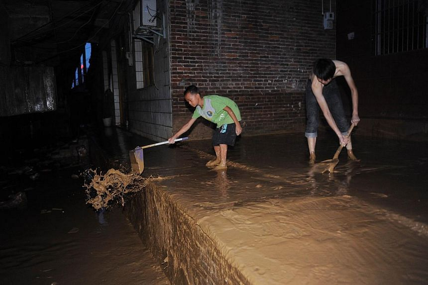 This picture taken on Aug 17, 2013, shows local residents cleaning their home flooding hit Ningyuan county of Yongzhou, central China's Hunan province. Heavy rains killed 21 more people as flooding spread to north-west China, state media said on Wedn