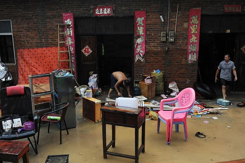This picture taken on Aug 17, 2013, shows local residents organising their furniture after flooding hit Ningyuan county of Yongzhou, central China's Hunan province. Heavy rains killed 21 more people as flooding spread to north-west China, state media