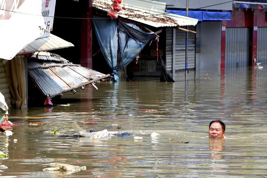 A man swims in a flooded street under the influence of Typhoon Utor in Shantou, Guangdong province, on Aug 20, 2013. Heavy rains killed 21 more people as flooding spread to north-west China, state media said on Wednesday. Severe weather in other part