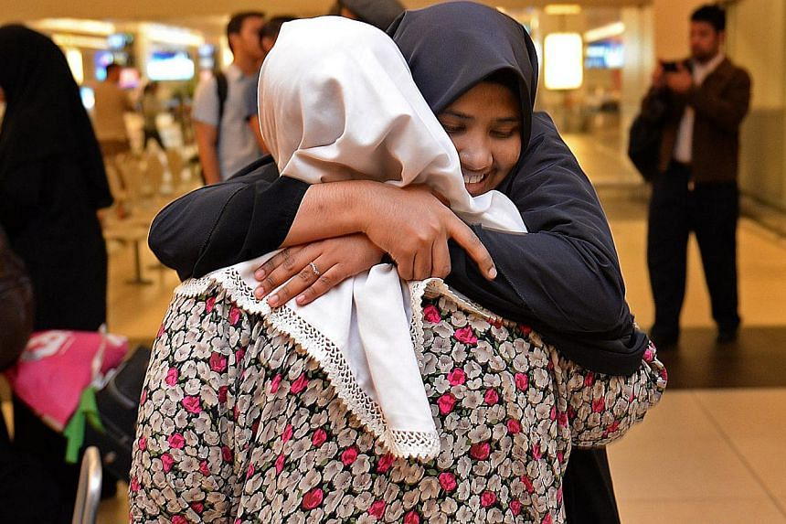 Ms Sakinah Mohamed Noordean hugs her mother, Madam Latifa Buang, at Changi Airport this morning.Over 20 Singaporean students from Egypt arrived in Singapore on Aug 21, 2013, having evacuated the country following unrest and mass demonstrations that h