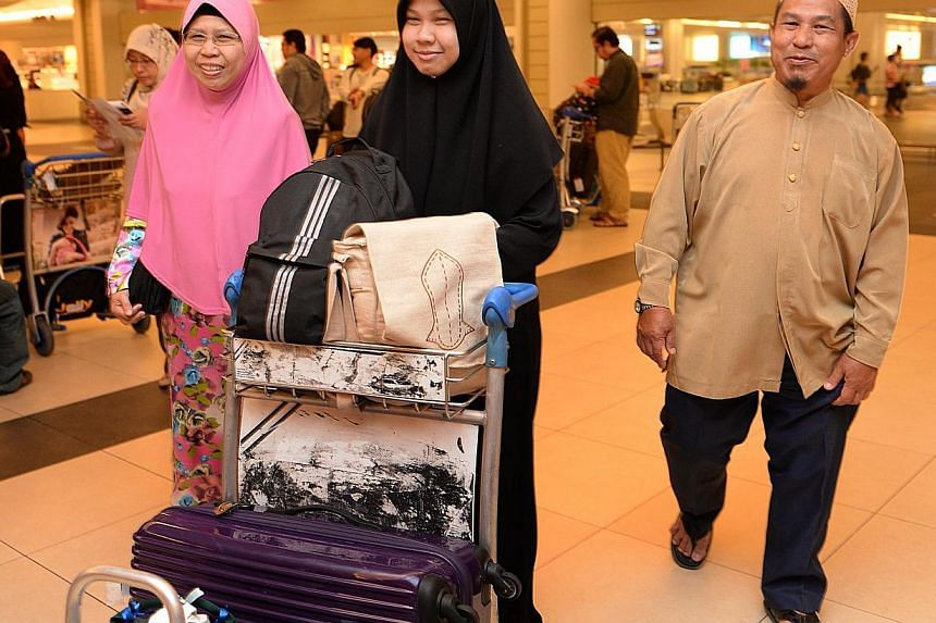 Ms Nur Hidayah Mohd Ismail (centre) with her mother Jemilal Hassan (left) and father Mohd Ismail Abu Samah at Changi Airport on Aug 21, 2013. Ms Nur Hidayah is among the Singaporean students studying in Egypt who arrived in Singapore on Wednesday mor