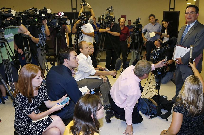 Prosecutor Jason Hicks, right, talks to the media following a court appearance for three teenagers charged in the death of Christopher Lane in Duncan, Oklahoma, on Tuesday, Aug 20, 2013. Lane, an Australian who was on a baseball scholarship at East C