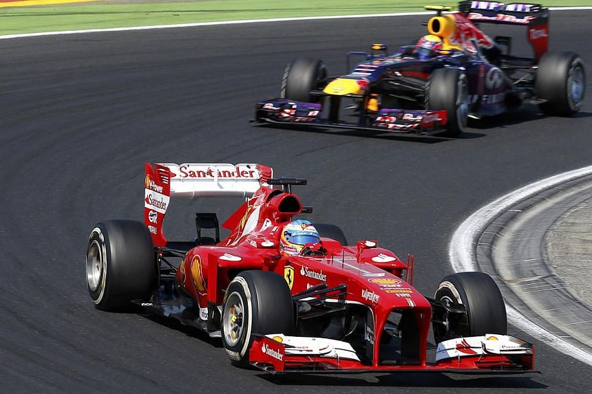 Ferrari driver Fernando Alonso drives ahead of Red Bull driver Mark Webber during the Hungarian Grand Prix at the Hungaroring circuit in Mogyorod on July 28, 2013. Ferrari have not given up hopes of winning the Formula One world drivers' title despit