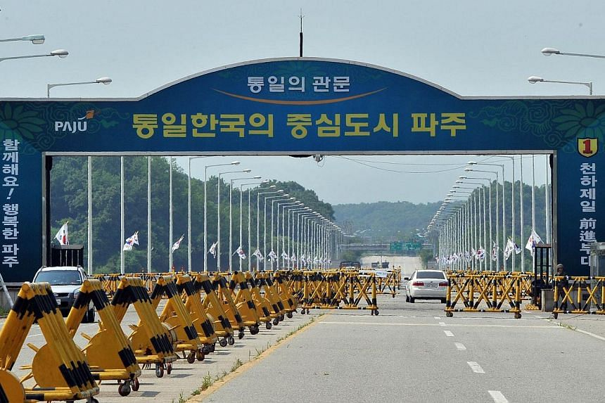 Cars drive past barricades on the road linking North Korea's Kaesong Industrial Complex at a military check point in Paju near the demilitarized zone dividing the two Koreas on June 6, 2013. South Korea's pointman on North Korea on Wednesday, Aug 21,