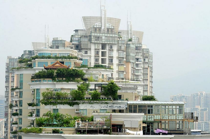 A temple (left) is seen on the rooftop of a 21-storey apartment building in Shenzhen, south China's Guangdong province on Wednesday, Aug 21, 2013. Surrounded by foliage, the temple has glazed golden tiles and traditional upturned eaves with carvings