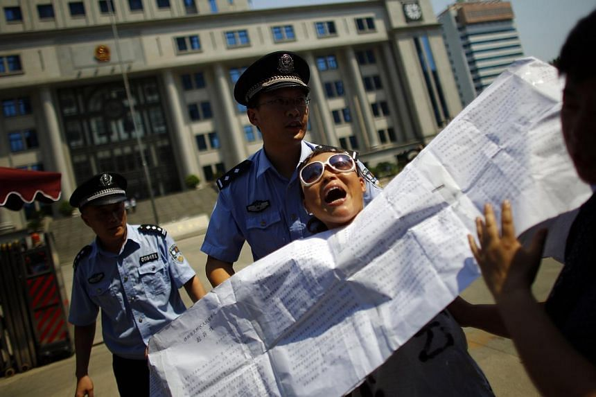Policemen remove a petitioner outside the court where the trial of disgraced Chinese politician Bo Xilai will be held on Thursday, Aug 22, 2013, in Jinan, Shandong province on Wednesday. A handful of Bo's supporters protested on the eve of his trial