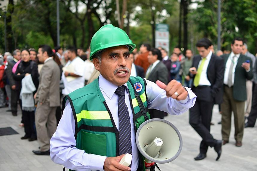 Employees of the foreign ministry evacuate the building after a 6.1 magnitude earthquake shook Mexico City on Wednesday, Aug 21, 2013. Its epicentre was located in the poor southern state of Guerrero, the United States Geological Survey (USGS) said,