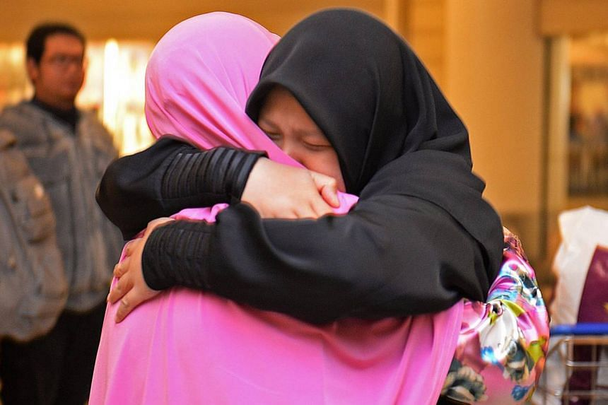 Ms Nur Hidayah Mohd Ismail (in black) hugs her mother, Madam Jemilal Hassan, at Changi Airport on Aug 21, 2013. Over 20 Egypt-based Singaporean students reunited with their families shortly after arrival on Wednesday morning. -- ST PHOTO: RAJ NADARAJ