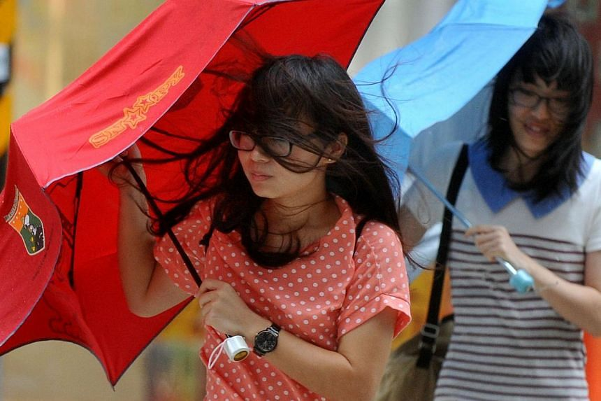 Pedestrians battle against strong winds caused by Tropical Storm Trami in Taipei on Aug 21, 2013. -- PHOTO: AFP