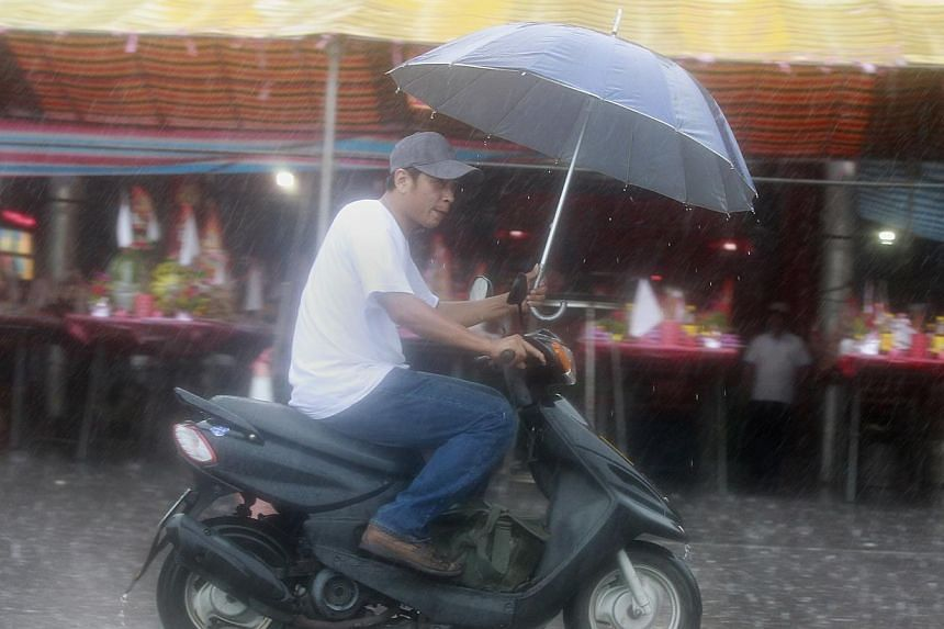 A man holding an umbrella rides a motorcycle as Tropical Storm Trami approaches the north-eastern coastal town of Nanfangao in Ilan county on Aug 21, 2013. -- PHOTO: AFP