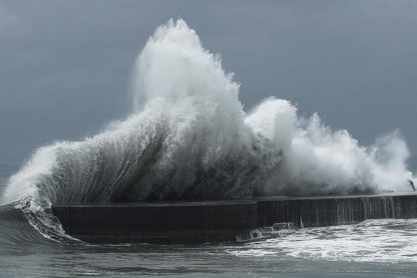 Massive waves from approaching Tropical Storm Trami slam into breakwaters near Toucheng, north-eastern Taiwan on Wednesday, Aug 21, 2013. -- PHOTO: REUTERS