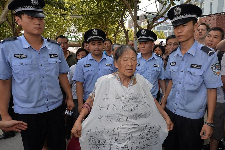 Police surround a protester outside the Intermediate People's Court where disgraced politician Bo Xilai will soon go on trial in Jinan, Shandong province, on Aug 21, 2013. Protesters gathered outside a courthouse in eastern China on Wednesday in hope